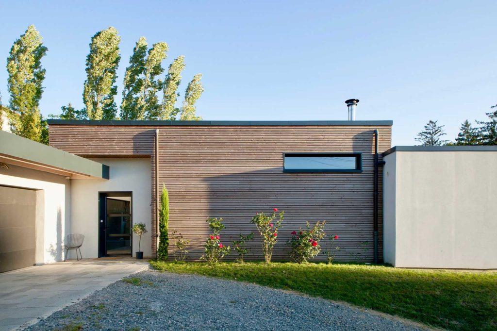 Les constructions en ossature bois peuvent être résolument moderne et design. C'est la cas de cette maison moderne à Limonest construite par Itinéraire Bois. Elle épouse des formes géométrique et sobres jusque dans l'allée extérieure. L'alliance du bois, de la pierre et de la végétation offre un aspect résolument moderne à cette habitation sur-mesure