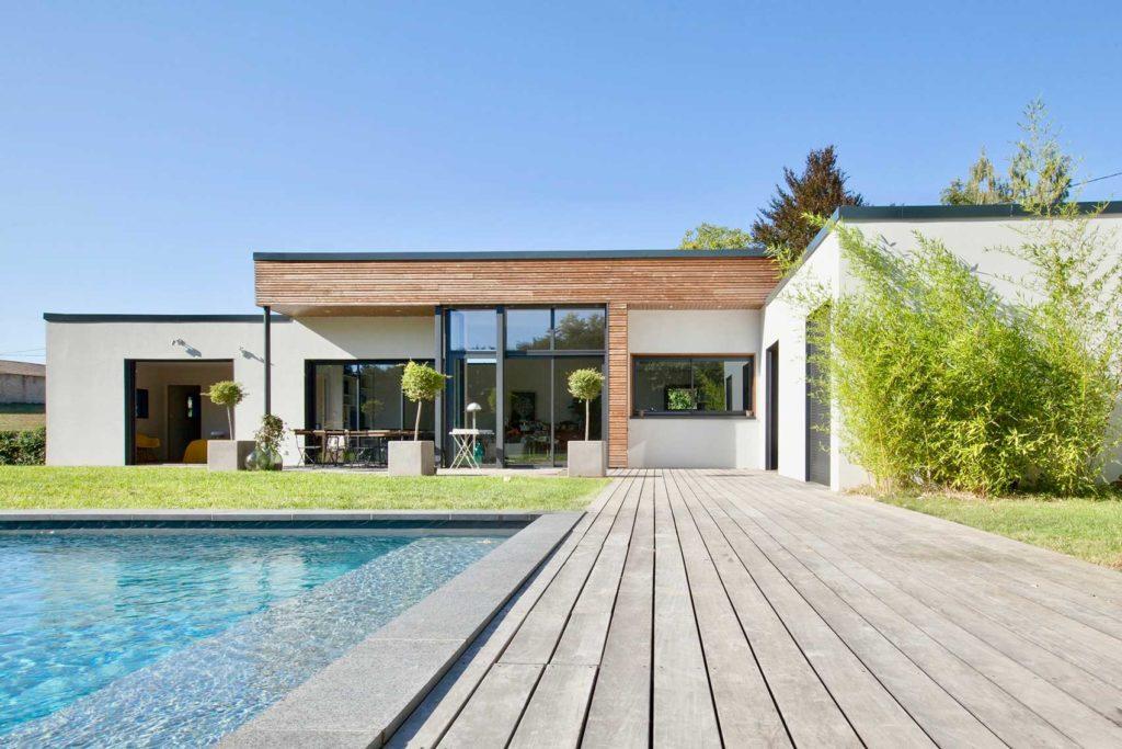 Découvrez cette magnifique construction : Une maison moderne conçue sur-mesure par itinéraires Bois. Au toit plat, avec une belle terrasse et une grande piscine, cette maison s'inscrit parfaitement dans le paysage local tout en bénéficiant de tous les avantages de l'ossature bois.
